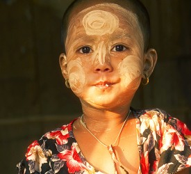 A young girl with her decorative sunscreen.